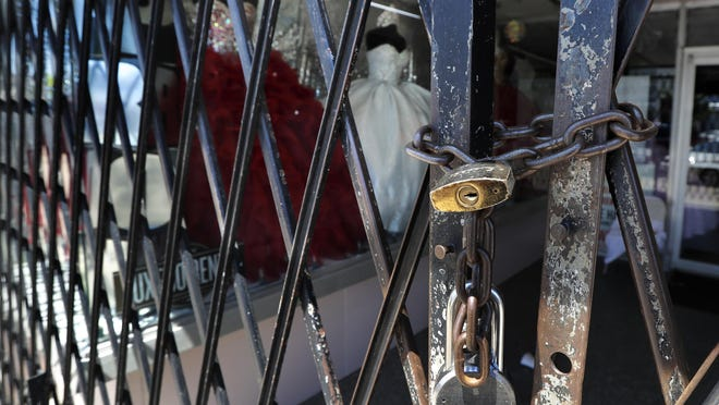 Formal dresses sit behind a locked entry at a business along Jefferson Boulevard, a normally busy shopping district in Dallas, Wednesday, April 15, 2020. (AP Photo/Tony Gutierrez)