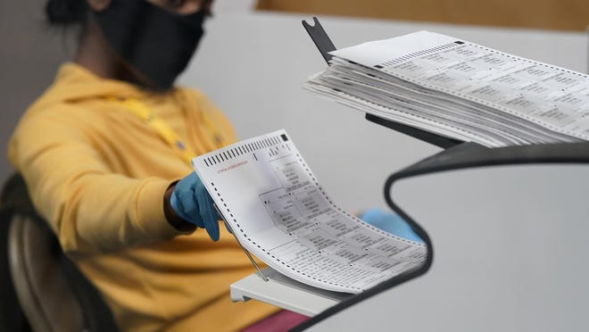 A county election worker scans mail-in ballots at a tabulating area at the Clark County Election Department, Thursday, Nov. 5, 2020, in Las Vegas.