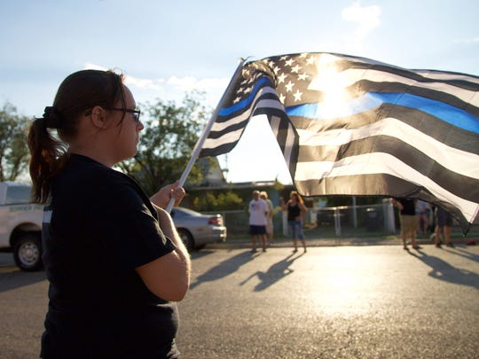 An Alamogordo resident holds an American blue line flag as the motorcade for fallen Alamogordo police officer Clint Corvinus passing by Saturday.