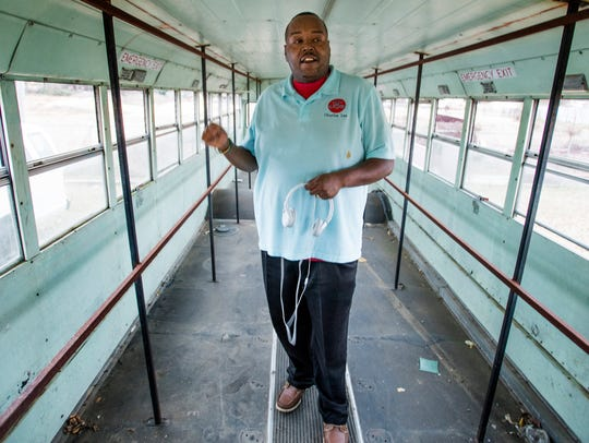 Charles Lee shows off a school bus that will be turned