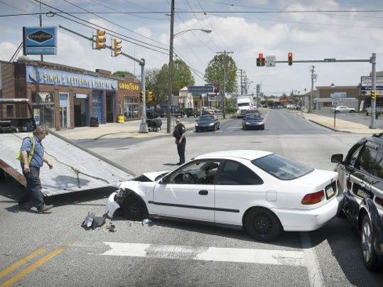 A tow truck driver maneuvers a car damaged in a crash at 12:48 p.m. Thursday at 16th and Cumberland streets in North Cornwall Township onto the bed of his truck. Three vehicles were involved in the crash.