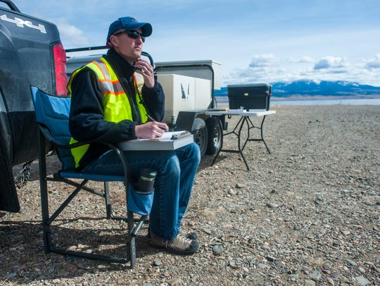 Adam Strainer, fisheries technician, sits by a watercraft inspection station near Silos Campground a year ago.