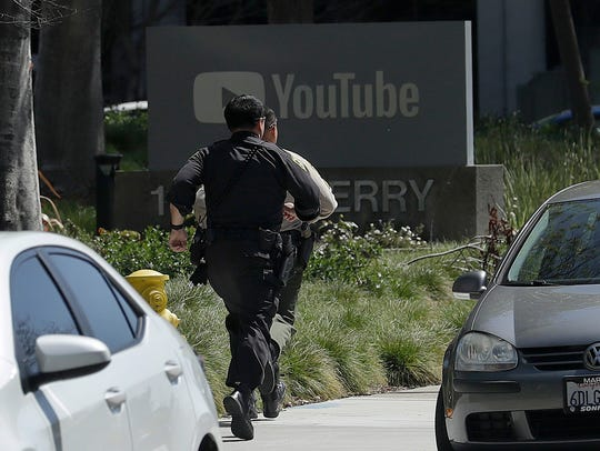 Officers run toward a YouTube office in San Bruno,