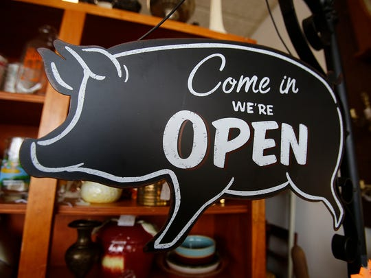 A pig-shaped open sign is among the eclectic offerings at the Fawn and Fox consignment store on the Indianola Square. Mark McCaughey owns the Fawn and Fox with his father Mac McCaughey.