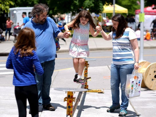 Lyra Bales, 6, walks a tight rope with the aid of her father, Christopher, and mother, Kelly, during the Children's Festival of Reading at World's Fair Park on Saturday, May 21, 2016.