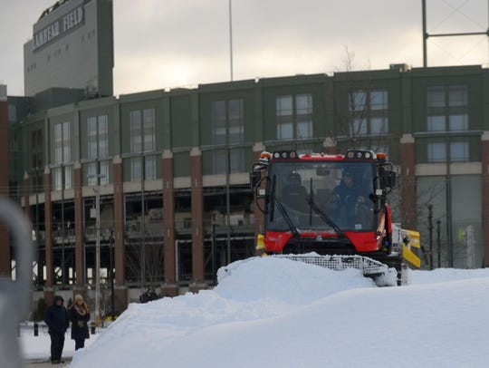 Workers prepare the Ariens Hill snow-tubing run in