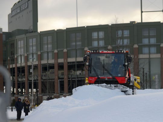 Workers prepare the Ariens Hill snow-tubing run in the Green Bay Packers Titletown District on Friday, Dec. 15, 2017. The Packers expect to open the hill next week.