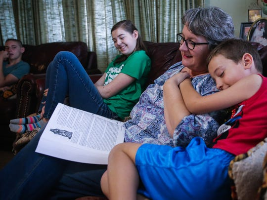 Egan, 6, snuggles up to his mother, Deja Armstrong, while she reads history Tuesday, April 3, 2018, at their San Angelo home.
