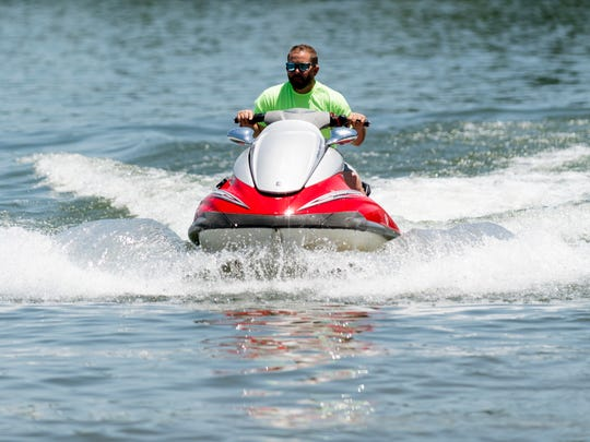 Scott Payne, owner of the Jungle Float, rides on his jet ski at Rocky Point Park in Farragut, Tennessee on Thursday, June 7, 2018. Jungle Float is a floating, 35-foot water park featuring a rope swing two launching trampoline platforms, a diving board, a high-jump platform, and a water slide.
