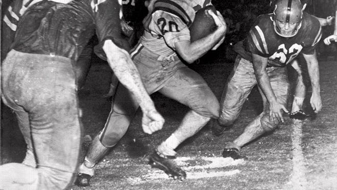 Billy Cannon, Louisiana State University's All-America halfback, slips by tacklers at the start of an 89-yard punt return for a touchdown to help his champion Tigers beat third-ranked Ole Miss, 7-3, Oct. 31, 1959, in Baton Rouge, La.