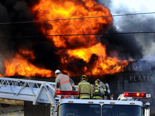 Firefighters set up rigs to help battle a fire at Adams