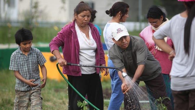 File photo: Sujan Gurung, left, approaches the hose held by his aunt, Gita, who is helping Sujan's uncle, Ram, wash his hands at a Lexington Avenue community garden in Rochester. The urban farm serves refugees, many from Nepal, living in northwest Rochester.
