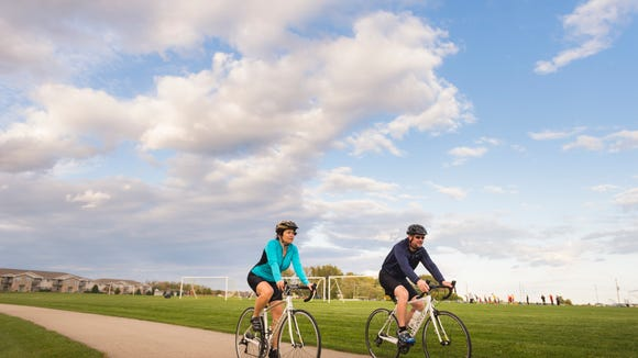 While their son, Cooper, attends soccer practice, Hanna and Joel Helein ride their bikes to get some exercise.