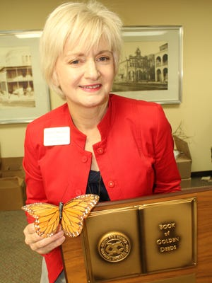 """Selma-Dallas County Chamber of Commerce Director Sheryl Smedley holds her """"Book of Golden Deeds"""" award and a model butterfly signifying the town as Alabama's Butterfly Capital."""