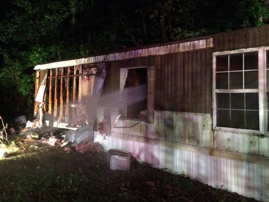 Firefighters extinguish a house fire in Angola Neck