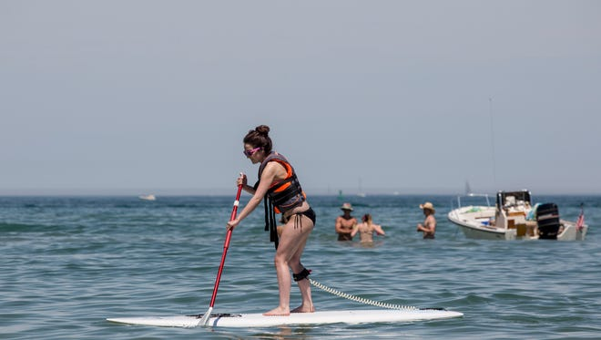 Ashley Fage, 19, of Port Huron, tries out a stand up paddleboard from Missy's Kayak Connection and PoHo Paddle Saturday, June 18, 2016 at Lakeside Beach in Port Huron.