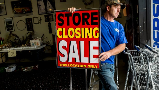 Co-owner Jason Small, of Port Huron, carries a 'store closing' sign outside Tuesday, September 20, 2016 at Bargain Barn in Port Huron. The business will close this Saturday after five years.
