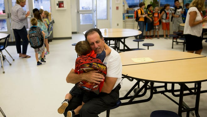 Everglades City School principal Jim Ragusa greets students as they make their way into school Monday, Sept. 25, in Everglades City, Fla., 15 days after Hurricane Irma made landfall students from southeastern Collier county came closer to a sense of normalcy as they returned to Everglades City School for their first day back since the storm.