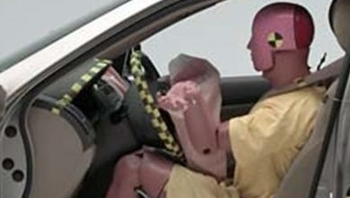 An air bag deploys in an older Honda Accord in a test crash
