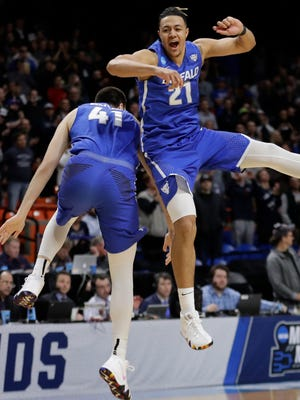 Buffalo's Dominic Johnson, right, and Brock Bertram celebrate after Buffalo upset Arizona 89-68 in first-round game in the NCAA men's college basketball tournament Thursday.