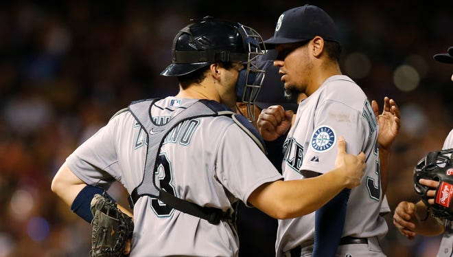 Seattle Mariners starting pitcher Felix Hernandez, right, meets with catcher Mike Zunino as Hernandez is pulled from the mound against the Colorado Rockies in the seventh inning of an inter league baseball game Monday, Aug. 3, 2015, in Denver.