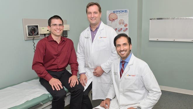 JFK nurse and stroke patient Phillip Castillo (left) at a follow-up appointment with Dr. Thomas Steineke (center), Chief of Neurosurgery and Director of Pediatric Neurosurgery at JFK Neuroscience Institute, and Dr. Jarad Kirmani, Director of JFK's Stroke & Neurovascular Center.