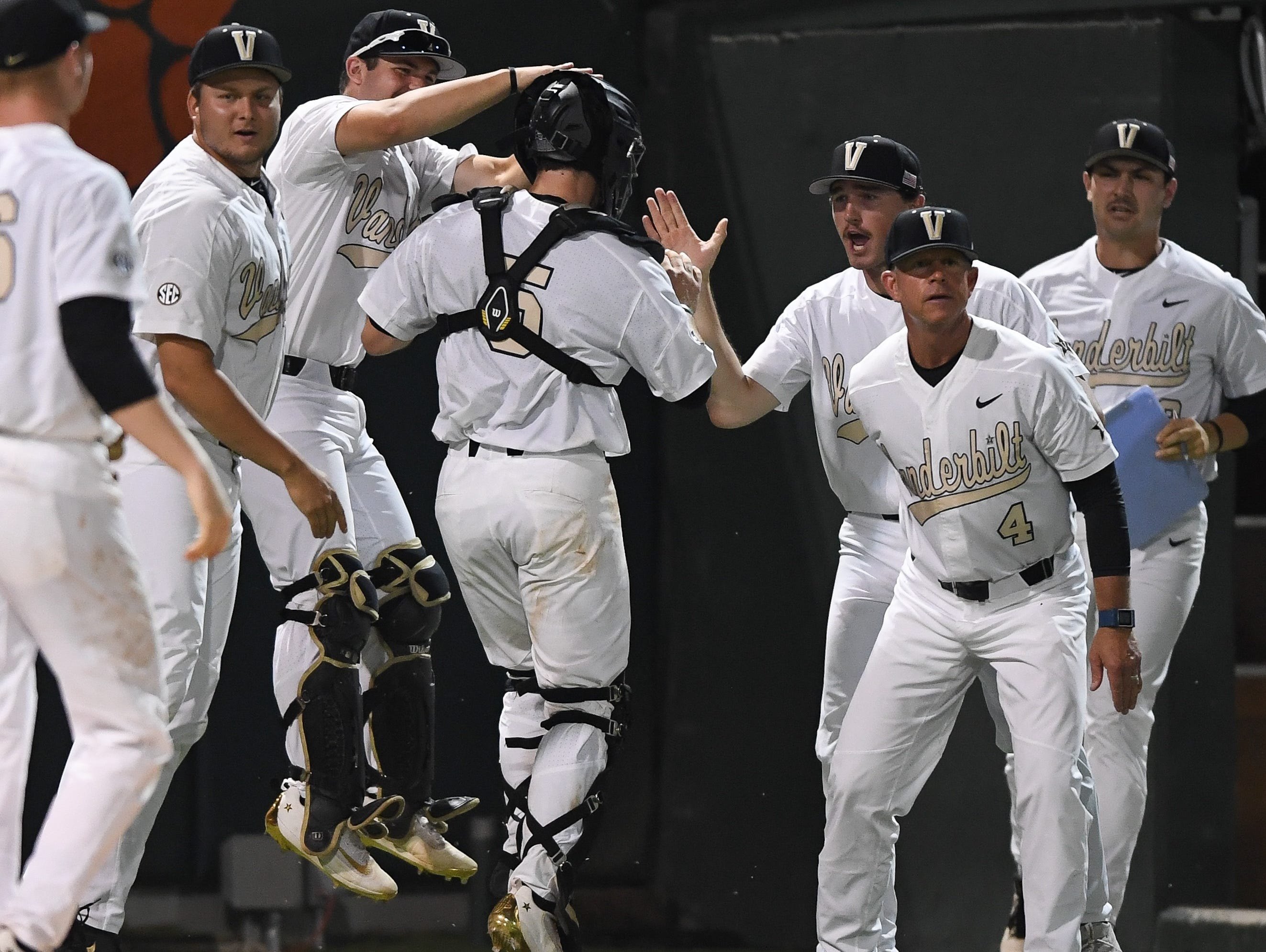 Vanderbilt catcher Jason Delay, center, celebrates an out at home plate with teammates and coaches during an NCAA Regional game versus host Clemson Sunday night.