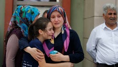 Family members of victims cry outside the Forensic