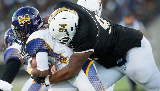 Alabama State's Roderick Henderson (94) wraps up Miles College's Christian Mays (6) during the Turkey Day Classic at ASU Stadium in Montgomery, Ala. on Thursday November 24, 2016.