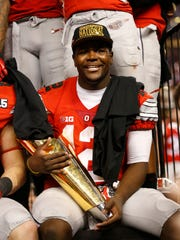 Ohio State Buckeyes quarterback Cardale Jones (12) holds the College Football Playoff trophy after the game against Oregon Ducks in the 2015 CFP National Championship Game at AT&T Stadium.