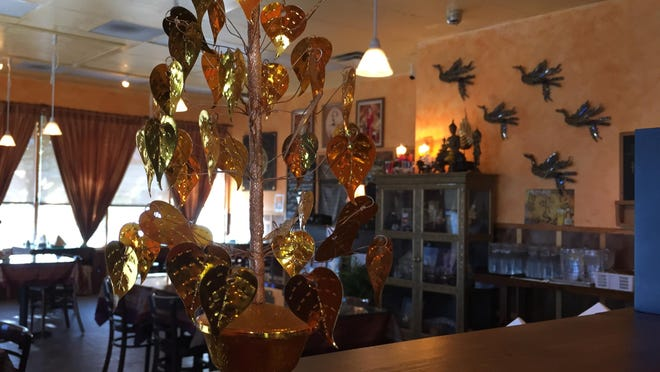 The art-filled dining room at Thai Lotus in south Reno stretches beyond an ornamental arrangement of golden leaves.
