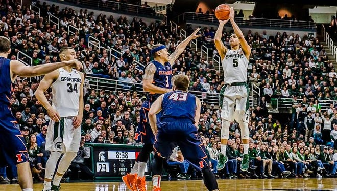 Bryn Forbes, of MSU, lines up a successful 2-point attempt over Illinois defender Khalid Lewis during their game Thursday in East Lansing.