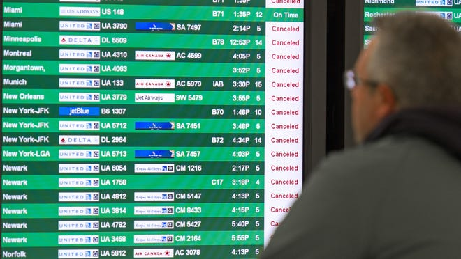 "A man looks at a flight status screen flashing ""Canceled"" notices for most flights at Dulles International Airport on Feb. 13, 2014, near Washington, D.C."