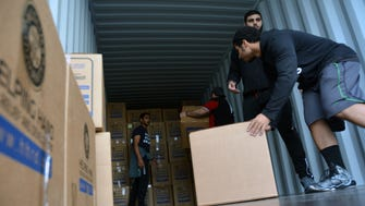 Volunteers at Helping Hand for Relief and Development load boxes into a shipping container, which will be sent off to countries with refugees in need of help.