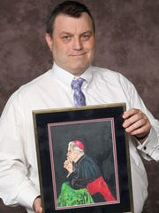 Brian Liddle holds his colored pencil drawing of Archbishop Fulton J. Sheen in prayer.