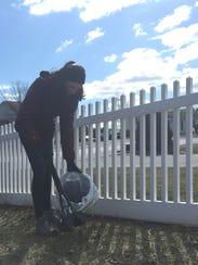 Savannah Kirby scoops dog poop at a home in Stewartstown.