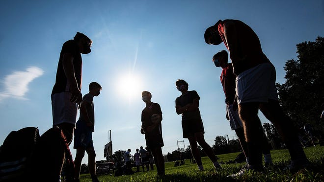 Silhouette of varsity and junior varsity players, wearing their masks, catch up on things before the start of boys soccer practice at Holy Ghost Prep in Bensalem, on Tuesday, Aug. 25, 2020.