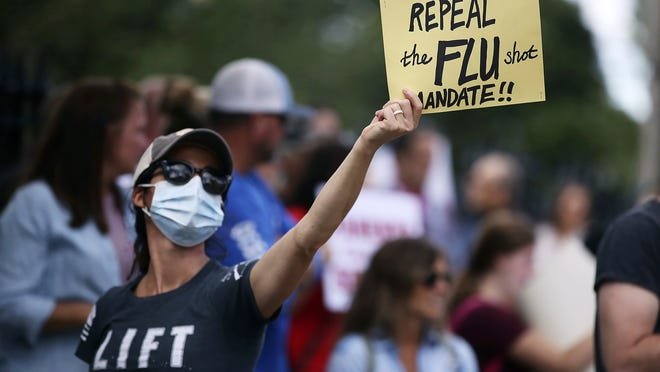 Teresa Hays, of Clinton, holds a sign during a protest against mandatory flu vaccinations, outside the Massachusetts State House, Sunday, Aug. 30, 2020, in Boston. Public health authorities say flu shots are very important this year to avoid overburdening the health system. amid the coronavirus pandemic.