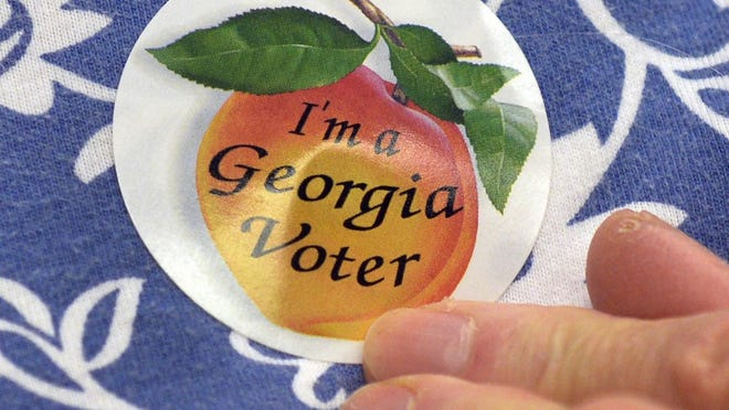 Nancy Tuttle  wears her I''m a Georgia Voter' sticker after voting in a past election.