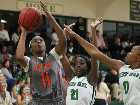 Dunbar's Danasia Fennie looks to score on Fort Myers players Autumn Giles and Bethany Brunson in the second half of the Dunbar at Fort Myers girls basketball game.