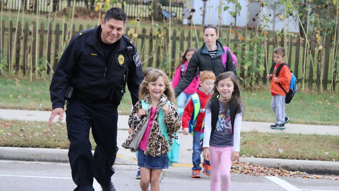Eagle Police Chief Gregg Duran leads Eagle Elementary School students Kennedy Basterash and Carly Callan over the crosswalk.