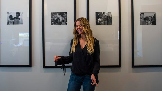 Amy Brown laughs in front of framed pictures of the two children she and her husband are adopting from Haiti in their home in East Nashville on Monday, May 22, 2017. It has taken years for the adoption to be finalized, and the couple hope to bring their children home soon.