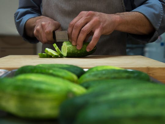 Chef Ryan Harrison slices cucumbers for a batch of
