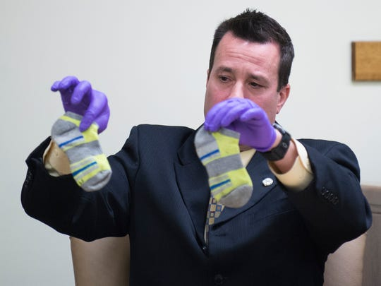 Det. Bill Rumell holds up socks 3-year-old Brendan Creato was wearing when his body was found during day six of testimony Wednesday, May 3, 2017 in Camden.