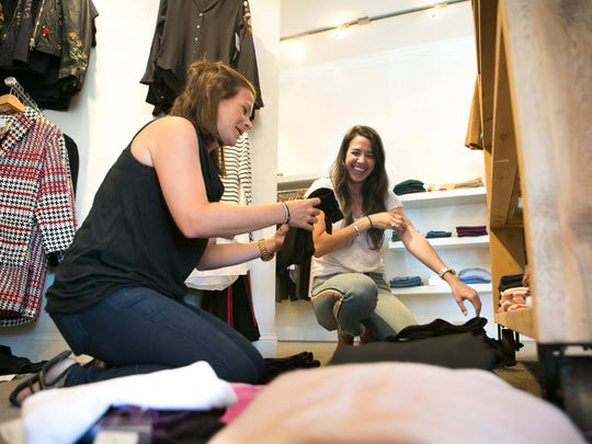 Sales associates Cindy Carmine (left) and Ashley Murphy put the final touches to Peter Kate, the women's boutique store that has moved from Greenville to the Fairfax Shopping Center on Concord Pike.