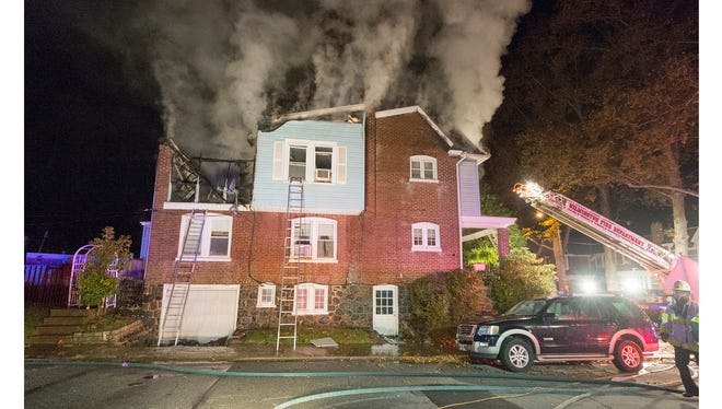 Firefighters battle a house fire at 16 W. 39th Street in Wilmington on Tuesday.