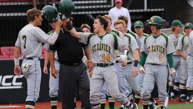 St. X's Chase Patton (14) celebrates with teammate Bryce Elmore (7) after he knocked him in with a 2-run homerun during their 7th Regional Championship game against Male at U of L's Patterson Stadium. 