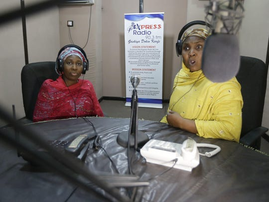 In this photo taken Tuesday April, 5. 2016 author Hadiza Nuhu Gudaji, left, during a radio talk show on her novels in Kano, Nigeria. In the local market stalls are signs of a feminist revolution with piles of poorly printed books by women, as part of a flourishing literary movement centered in the ancient city of Kano, that advocate against conservative Muslim traditions such as child marriage and quick divorces. dozens of young women are rebelling through romance novels, many hand-written in the Hausa language, and the romances now run into thousands of titles. (AP Photo/Sunday Alamba)