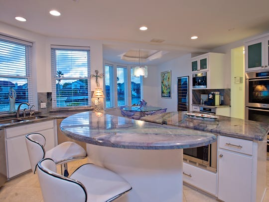 The kitchen is the hub for gatherings with family and friends with beautiful granite counters, island and backslashes, stainless appliances and water views, one can see why.