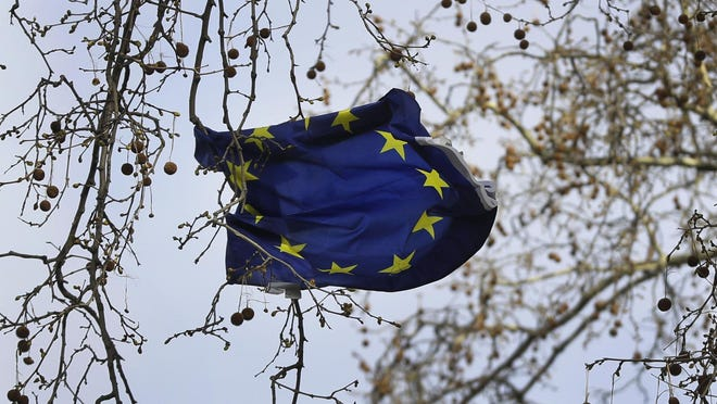 A European Union flag blows in the wind, caught on the branches of a tree near Parliament in London, Friday, March 15, 2019. British Prime Minister Theresa May is working to pull off an against-the-odds rescue for her European Union divorce deal, after Parliament voted to postpone Brexit to avert a chaotic U.K. departure in two weeks.